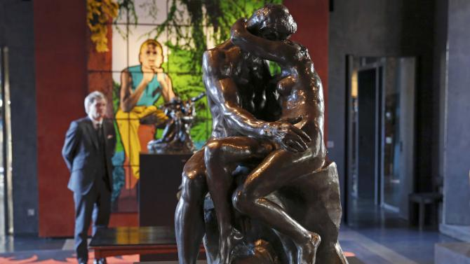 """Auctioneer Alexandre Giquello looks at the sculpture """"Le Baiser"""" which is part of an exceptional sale of five remarkable bronzes by the French sculptor Auguste Rodin, displayed in Paris"""