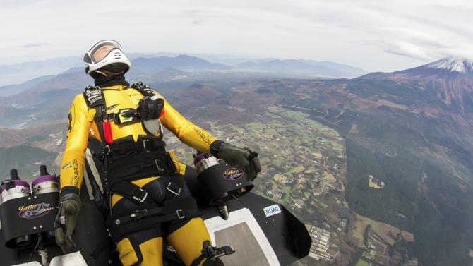 Yves Rossy, known as the Jetman, drops from a helicopter to fly near Mount Fuji