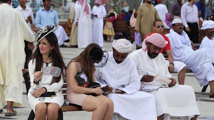 a woman in western dress helps an Arab to go through the race catalogue, during the Dubai World Cup horse race, Saturday, March 31, 2012, in Dubai, United Arab Emirates. (AP Photo/Kamran Jebreili)