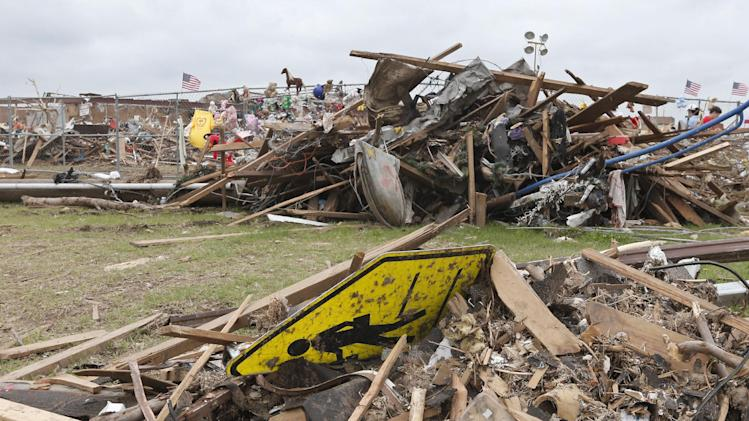 A school crossing sign is lodged in the tornado rubble outside Plaza Towers elementary school in Moore, Okla., Monday, May 27, 2013. (AP Photo/Sue Ogrocki)