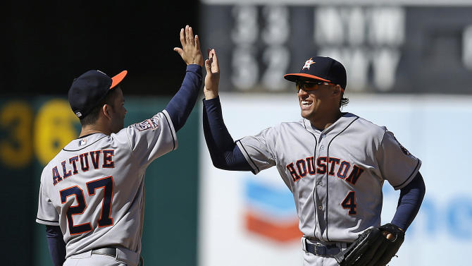 Houston Astros' Jose Altuve, left, and George Springer celebrate the 9-3 defeat of the Oakland Athletics at the end of a baseball game Saturday, April 25, 2015, in Oakland, Calif. (AP Photo/Ben Margot)