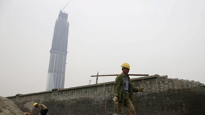 Labourers work at the construction site of an official building next to the unfinished 438-metre-high Wuhan Centre in Wuhan