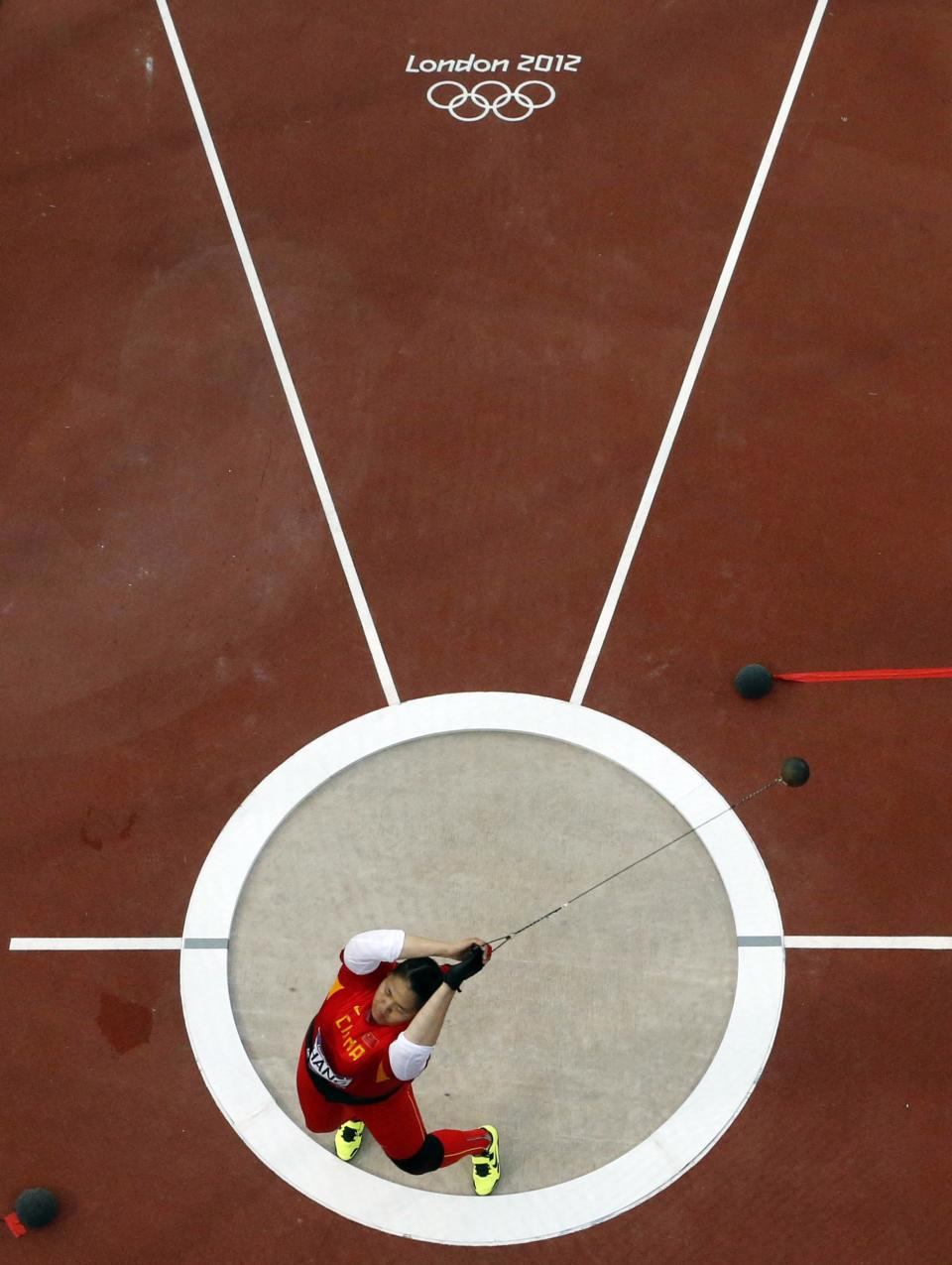 China's Zhang Wenxiu competes in the women's hammer throw final during the 2012 Summer Olympics at the Olympic Stadium, Friday, Aug. 10, 2012, in London. (AP Photo/Pawel Kopczynski, Pool)