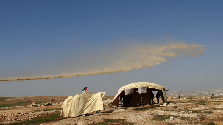 Israeli security forces spray Palestinian activists with a chemical which leaves a bad odor in Yatta, south of the West Bank city of Hebron, Saturday, Feb. 9, 2013. Palestinian activists set up a tent village to protest the settlement building in the area. (AP Photo/Nasser Shiyoukhi)