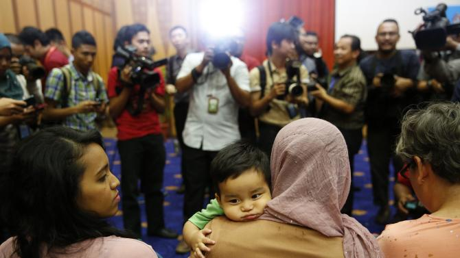 A woman carries a baby boy, who is the son of flight attendant Mohd Hazrin Hasnan aboard the missing Malaysia Airlines Flight MH370, at a news conference in Putrajaya