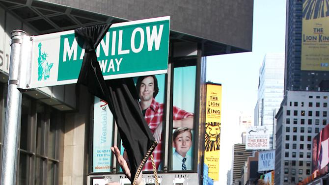 """This image released by Starpix shows Barry Manilow unveiling a street sign reading Manilow Way in Times Square, Tuesday, Jan. 22, 2013 in New York. Manilow is performing in """"Manilow on Broadway,"""" until Feb. 23 at the St. James Theatre. (AP Photo/Starpix, Kristina Bumphrey)"""