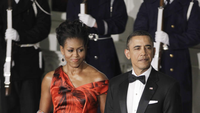 FILE - This Jan. 19, 2011 file photo shows President Barack Obama and first lady Michelle Obama at the North Portico of the White House in Washington as they the arrival of China's President Hu Jintao  for the State Dinner. Michelle Obama is wearing a fiery red gown designed by Alexander McQueen. Obama has proven her fashion savvy time and time again since she was introduced to the country as first lady on Inauguration Day 2009. In the past four years she has adeptly walked the line between directional fashionista and everywoman. (AP Photo/Charles Dharapak, file)