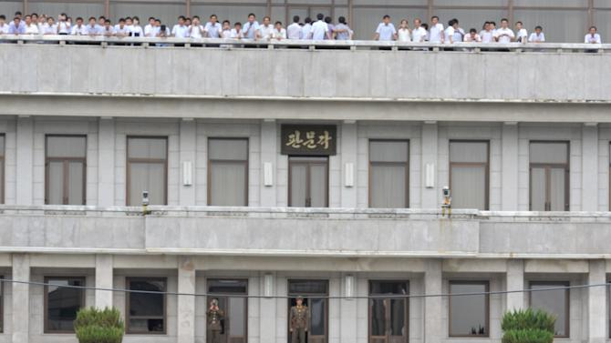 North Korean tourists, top on balcony, look at U.S. Army Gen. James Thurman, center bottom, and other U.S. and U.N. military officers who visited the truce village of Panmunjom to mark the 58th anniversary of the cease-fire of the 1950-53 Korean War, in the demilitarized zone separating the two Koreas on Wednesday July 27, 2011.  Thurman, the commander of the U.S. forces in South Korea, attended a ceremony commemorating the cease-fire. (AP Photo/Kim Jae-hwan, Pool)