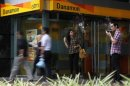 A man smokes a cigarette near a Danamon Bank ATM in Jakarta