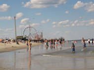 Bathers play in the surf in Seaside Park, N.J. on June 23, 2012. New Jersey's Top Ten beaches contest is suspending voting this summer on the best beach in the state, focusing instead on cooperation among regional tourism leaders to promote the shore as a whole as it recovers from Superstorm Sandy. In the background is the Funtown Pier in Seaside Heights, N.J. that was damaged in the storm. (AP Photo/Wayne Parry)