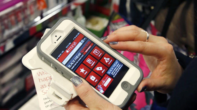Tashalee Rodriguez, of Boston, uses a smart phone app while shopping at Macy's in downtown Boston, Friday, Nov. 23, 2012. Retailers have been trying everything they can to lure consumers into stores. Some stores tested the earlier hours last year, but this year more retailers opened their doors late on Thanksgiving or at midnight on Black Friday. In addition to expanding their hours, many also are offering free layaways and shipping, matching the cheaper prices of online rivals and updating their mobile shopping apps with more information. (AP Photo/Michael Dwyer)