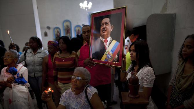 "Venezuelan embassy workers hold up a framed image of Venezuela's ailing President Hugo Chavez during the monthly Catholic service devoted to the sick at the Church of Our Lady of Regla, in Regla, across the bay from Havana, Cuba, Tuesday, Jan. 8, 2013. Venezuela's government said Monday, Chavez is in a ""stable situation"" in a Cuban hospital receiving treatment due to a severe respiratory infection. The update came as other government officials reiterated their stance that the president need not be sworn in for a new term as scheduled this Thursday and could instead have his inauguration at a later date. (AP Photo/Ramon Espinosa)"