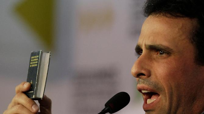 """Opposition leader Henrique Capriles holds up a copy of the Venezuelan Constitution as he speaks during a news conference in Caracas, Venezuela, Wednesday, Jan. 9, 2013. Capriles condemned the Supreme Court's endorsement of delaying the inauguration. """"Institutions should not respond to the interests of a government,"""" he said. (AP Photo/Fernando Llano)"""