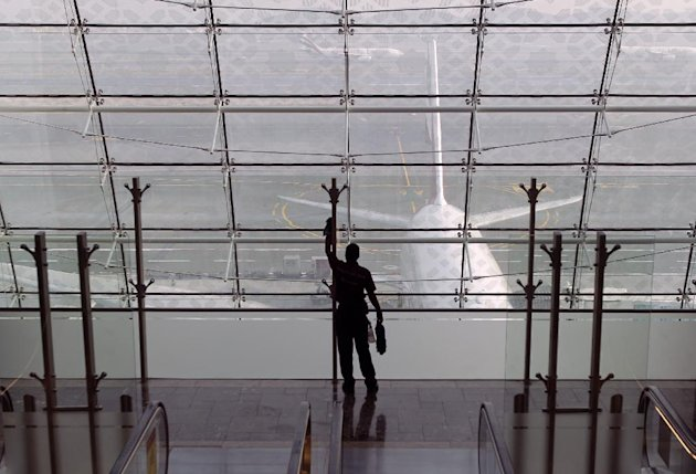 In this Sunday, Feb. 10, 2013, photo a laborer cleans a window at the new Concourse A of the Dubai airport in Dubai, United Arab Emirates. For generations, international fliers have stopped over in Lo
