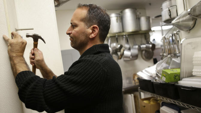 FILE - In this Monday, Oct. 8, 2012 file photo, Anthony Cavallo, owner of the restaurant Vintage 50, mounts a potato cutter in his restaurant in Leesburg, Va. U.S. service companies grew at a slightly slower pace in October than September because of a decline in new orders. But a measure of employment rose, indicating services firms hired more. The Institute for Supply Management said Monday, Nov. 5, 2012, that its index of non-manufacturing activity fell to 54.2. (AP Photo/Jacquelyn Martin, File)