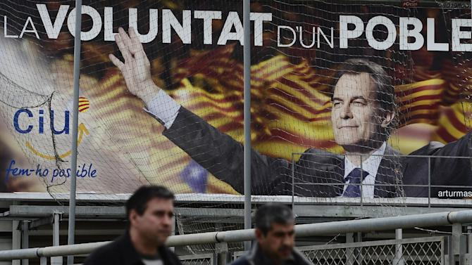 Two men walks in front of an electoral poster featuring the leader of center-right Catalan Nationalist Coalition (CiU) Artur Mas following Sunday's elections in Barcelona, Spain, Monday, Nov. 26, 2012. A day after voters in Spain's economically powerful region of Catalonia dealt a punishing blow to the ruling party advocating independence from Spain, the pressure was on the party leader and regional president Artur Mas to form a new government that would carry out his promise. (AP Photo/Manu Fernandez)