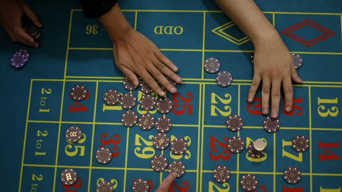 In this Oct. 25, 2012 photo, a gambling school students take practice on a table in Macau, China. Hordes of Chinese high rollers flooding into Macau have turned the city into an Asian casino boomtown but they're also posing a challenge for China's next generation of leaders.(AP Photo/Vincent Yu)