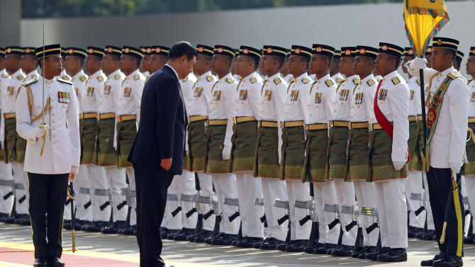 Chinese President Xi Jinping, foreground right, bows as he inspects a guard of honor during a welcoming ceremony at Parliament Square in Kuala Lumpur, Malaysia, Friday, Oct. 4, 2013. Xi is on a three-day state visit to Malaysia. (AP Photo/Lai Seng Sin)