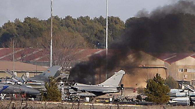 FILE - A Monday, Jan. 26, 2015 file photo showing smoke rising from a military base after a Greek F-16 fighter jet plane crash in Albacete, Spain. Loose papers left in the cockpit of an F-16 that crashed at a Spanish airbase could have sent the fighter jet into its deadly spiral, French investigators have concluded. The report released this week brings an end to a multinational investigation into what happened before the Greek plane's failed takeoff and crash.  (AP Photo/Josema Moreno, File)