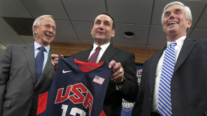Duke University basketball coach Mike Krzyzewski, center, holds a Team USA jersey, as he is flanked by school President Richard Broadhead, left, and Director of Athletics Kevin White at a news conference in Durham, N.C., Thursday, May 23 2013. Krzyzewski is back as the U.S. men's national team coach and ready for another run at Olympic gold. (AP Photo/The News & Observer, Corey Lowenstein)  MANDATORY CREDIT
