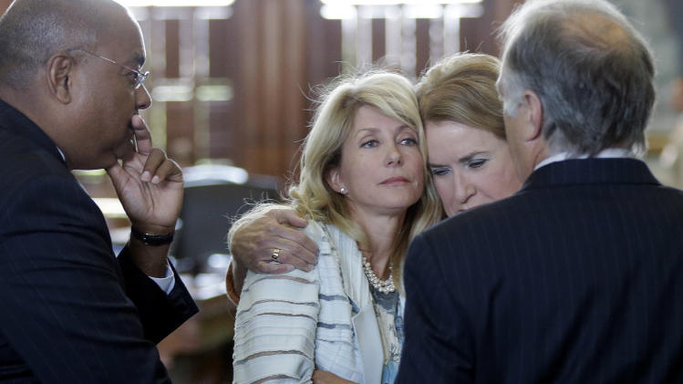Sen. Wendy Davis, D-Fort Worth, second from left, is hugged by Sen. Sylvia Garcia, D-Houston, as she prepares to filibuster an abortion bill, Tuesday, June 25, 2013, in Austin, Texas. The bill would ban abortion after 20 weeks of pregnancy and force many clinics that perform the procedure to upgrade their facilities and be classified as ambulatory surgical centers. With Davis is Sen. Rodney Ellis, left, and Sen. Kirk Watson, D-Austin, right. (AP Photo/Eric Gay)