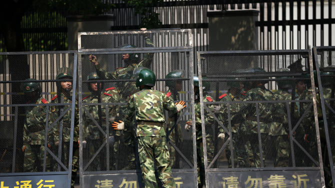 Paramilitary police officers arrange the steel fence at the Japanese Consulate General in Shanghai, China, Wednesday Sept. 19, 2012. China was returning to normalcy Wednesday after angry protests over Japan's wartime occupation and Tokyo's recent purchase of islands also claimed by Beijing. (AP Photo/Eugene Hoshiko)