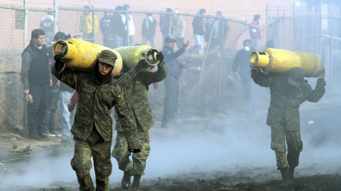 Soldiers remove household gas tanks that survived the fires and explosions after an oil pipeline exploded in San Martin Texmelucan, Mexico, Sunday Dec. 19, 2010.  An oil pipeline operated by Mexico's state-owned oil company Petroleos Mexicanos, or Pemex, exploded early Sunday when thieves were attempting to steal oil, killing at least 27 people, injuring at least 52 people and scorching more than 115 homes, authorities said.  (AP Photo/Rodolfo Perez)