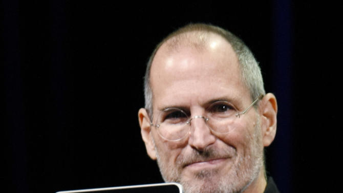 A Jan. 27, 2010 photo shows Apple CEO Steve Jobs holding up the new iPad during a product announcement in San Francisco. The iPad,is a portable device for reading books, watching video and surfing the Web. (AP Photo/Paul Sakuma)