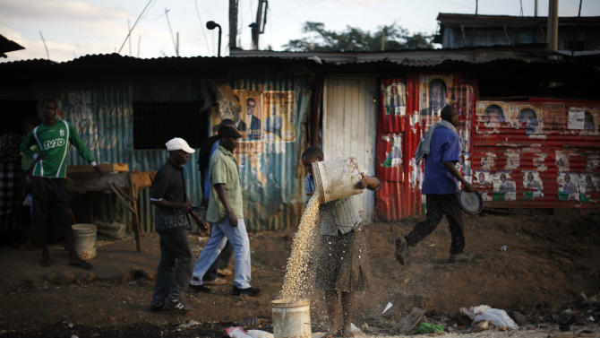 On International Women's day a Kenyan woman transfers corn as men walk by election posters- covered tin walls  in the street of  the Kibera slum of Nairobi, Kenya, Friday, March 8, 2013. Kenyans on Monday held their first presidential vote since the nation's disputed election in 2007 spawned violence that killed more than 1,000 people.  Kenya's last ballots for its presidential race were being counted Friday and Uhuru Kenyatta, the leading candidate, saw his percentage yo-yo above and below the crucial 50 percent mark that would hand him an outright win and avoid a runoff.(AP Photo/Jerome Delay)