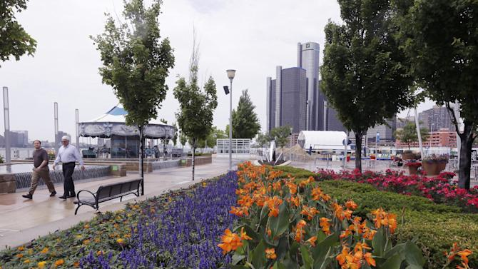 This June 24, 2014 photo shows walkers strolling on the Detroit RiverWalk in Detroit. Time was when the shores of the Motor City's majestic Detroit River, which separates it from the Canadian city of Windsor, were mostly industrial and uninviting. To make matters worse, Windsor's waterfront was verdant, pleasant and pedestrian-friendly. Then Detroit finally got some sense _ and some big donations _ to remodel its front door to the world and create the Detroit RiverWalk. Years of work have transformed much of it for recreational use. And it now includes William G. Milliken State Park & Harbor near downtown. (AP Photo/Carlos Osorio)