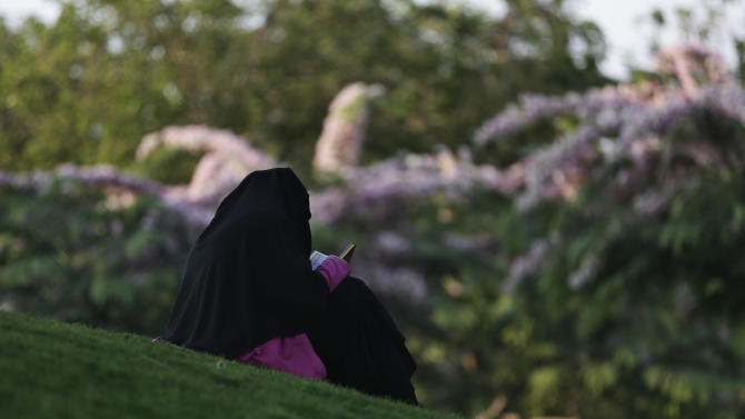A veiled Egyptian woman reads the Quran, Islam's holy book, before breaking her fast during the Islamic holy month of Ramadan at Al-Azhar Park, one of the bustling city's few public parks in Cairo, Egypt, Saturday, July 4, 2015. (AP Photo/Hassan Ammar)