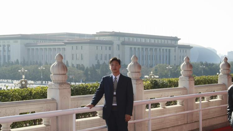 Chinese labour activist Zhang Zhiru poses for pictures at Tiananmen Square in Beijing