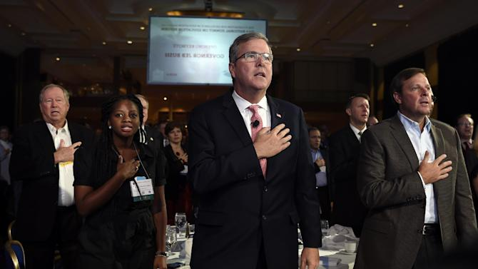 FILE - In this Nov. 20, 2014, file photo, former Florida Gov. Jeb Bush, center, recites the Pledge of Allegiance before giving the keynote address at the National Summit on Education Reform in Washington. Denisha Merriweather, second from left, who benefited from the Florida tax credit for education, introduced Bush. The faces of the Republican Party's most ambitious members are changing. Long criticized as the party of old, white, men, the GOP's next class of presidential contenders may include two Hispanic senators, an Indian-American governor, a female business leader and an African-American neurosurgeon. Among perhaps a dozen GOP White House hopefuls, all but a few are in their 40s and 50s. One of the oldest white men, Jeb Bush, is a fluent Spanish speaker whose wife is a native Mexican. Republicans say they're starting the 2016 presidential and congressional elections from a strong place after winning control of Congress a few weeks ago. But Democrats say that's misleading; the midterm electorate was older and whiter than in presidential elections. (AP Photo/Susan Walsh, File)