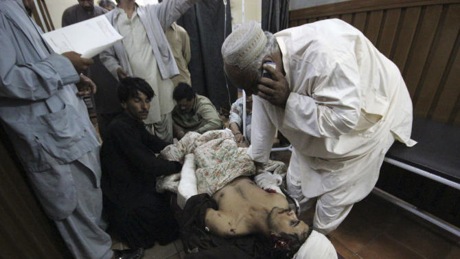 People comfort a man injured in a bomb blast in Sibi, about 150 kilometers (90 miles) east of Quetta, at a local hospital in Quetta, Pakistan on Thursday, Oct. 11, 2012. A powerful bomb blast in a market wounded dozens of people, senior police officer, Ghulam Aali Lashari said. (AP Photo/Arshad Butt).