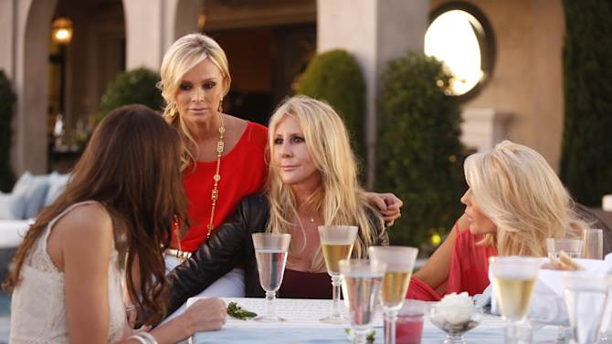 """This undated publicity photo provided by Bravo shows, from left, Heather Dubrow, Tamra Barney, Vicki Gunvalson and Gretchen Rossi, in a scene from """"All Housewives Clam Bake at Rachel's"""" in Bravo's Season Eight of """"The Real Housewives of Orange County."""" The TV series creator Scott Donlop, who cast Gunvalson, remembers her apprehension about joining the show like it was yesterday. At that point, nobody had any inkling """"The Real Housewives"""" would last for eight seasons, let alone ignite a cultural phenomenon. (AP Photo/Bravo, Vivian Zink)"""