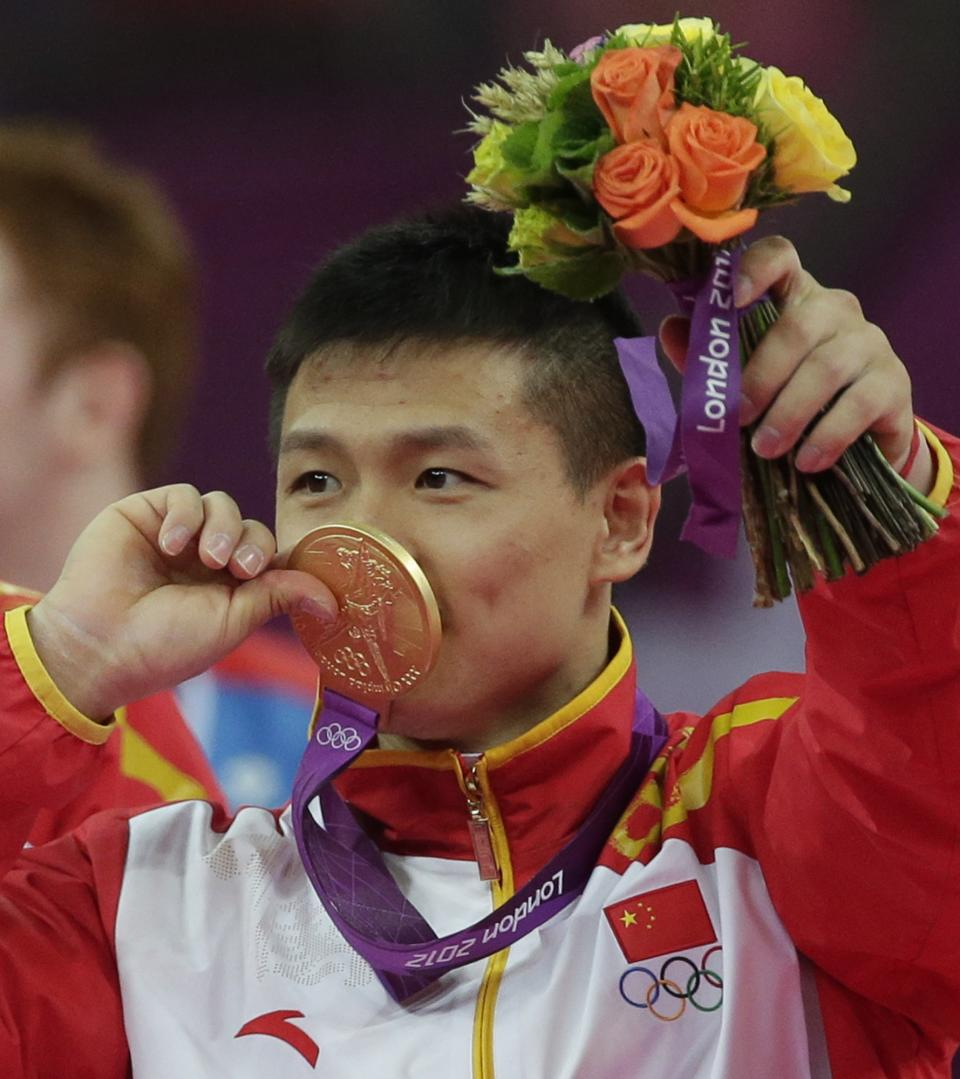 Chinese gymnast Chen Yibing kisses his gold medal after his team won the Artistic Gymnastic men's team final at the 2012 Summer Olympics, Monday, July 30, 2012, in London. (AP Photo/Julie Jacobson)