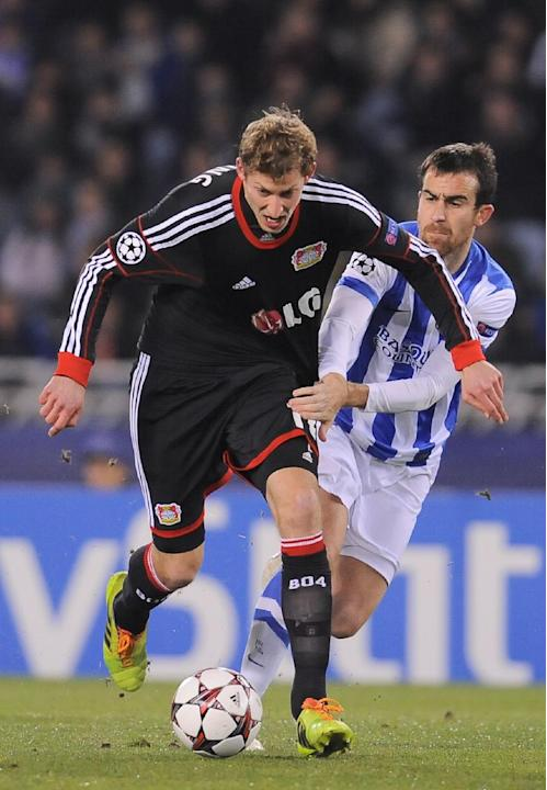 Leverkusen's Stefan Kiessling, left,  duels for the ball with Real Sociedad's Mikel Gonzalez, during their Champions League Group A soccer match at Anoeta stadium in San Sebastian, northern Sp