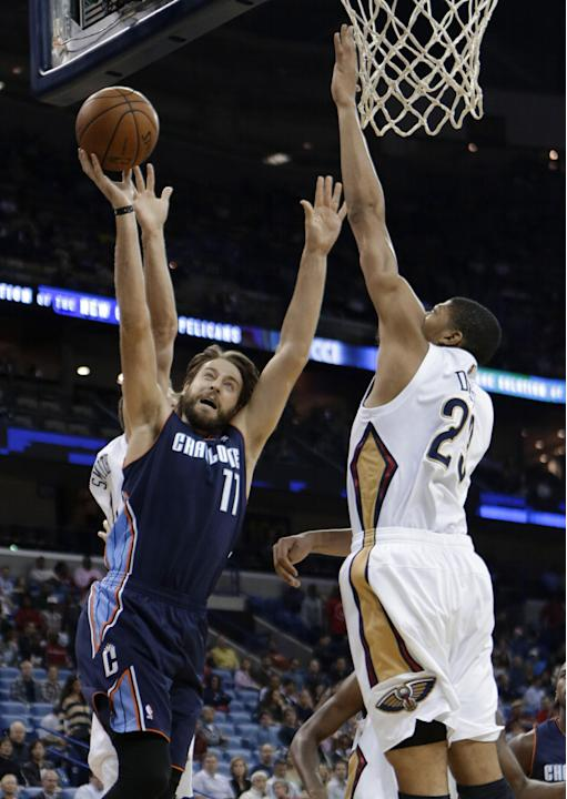 Charlotte Bobcats forward Josh McRoberts (11) drives to the basket between New Orleans Pelicans forward Anthony Davis (23) and New Orleans Pelicans forward Jason Smith, behind, in the first half of an