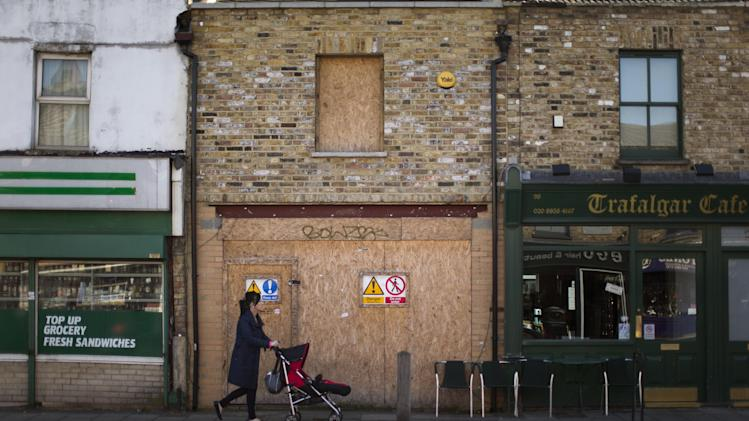 """**HOLD FOR DANICA KIRKA STORY - Britain High Street Lows** A woman pushes a child's buggy past a boarded up shop front on Trafalgar Road in Greenwich, London, Tuesday, March 5, 2013.  The small shopkeepers in Greenwich are running out of time.  In the London borough that gave its name to Greenwich Mean Time, businesses like Lorraine Turton's are in danger of being relegated to history _ the victims of online shopping, changing tastes and, increasingly, the protracted recession. Her Internet cafe on Trafalgar Road is a rare hive of activity on a """"high street"""" _ the British name for a town's main business district.  (AP Photo/Matt Dunham)"""