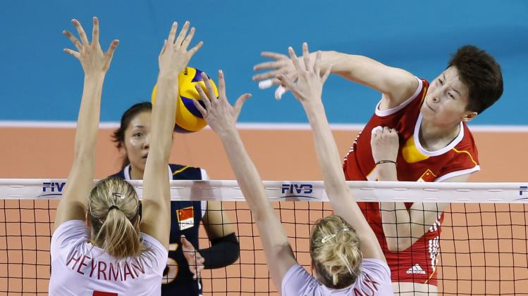 Li of China spikes the ball against Heyrman and Rousseaux of Belgium during their FIVB Women's Volleyball World Grand Prix 2014 final round match in Tokyo