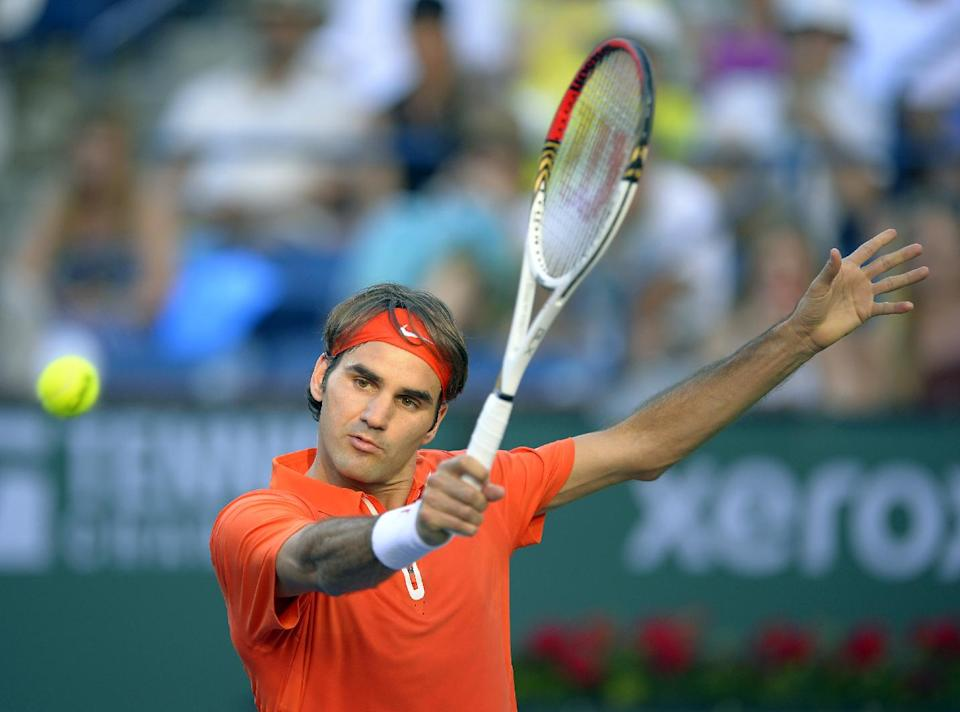 Roger Federer of Switzerland returns a shot against Stanislas Wawrinka of Switzerland during their match at the BNP Paribas Open tennis tournament, Wednesday, March 13, 2013, in Indian Wells, Calif. (AP Photo/Mark J. Terrill)