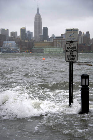 The Hudson River swells and rises over the banks of the Hoboken, N.J., waterfront as Hurricane Sandy approaches on Monday, Oct. 29, 2012. Hurricane Sandy continued on its path Monday, forcing the shutdown of mass transit, schools and financial markets, sending coastal residents fleeing, and threatening a dangerous mix of high winds and soaking rain. (AP Photo/Charles Sykes)