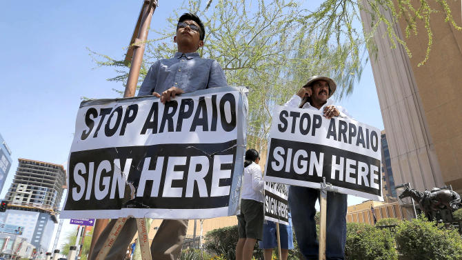 Simon Lopez, left, and Hiliaro Islas hold signs while trying to collect signatures in an effort to recall Maricopa County Sheriff Joe Arpaio, Wednesday, May 29, 2013 in downtown Phoenix. Organizers of a campaign aimed at ousting Arpaio face a deadline Thursday afternoon for handing signatures to force a recall election against the lawman. Recall organizers, who had trouble raising contributions and had to rely on volunteers rather than paid professionals to sign up supporters, face long odds in turning in more than 335,000 valid voter signatures. Arpaio critics are hoping a court ruling last week that Arpaio's office has racially profiled Latinos would draw out more supporters for their cause. (AP Photo/Matt York)