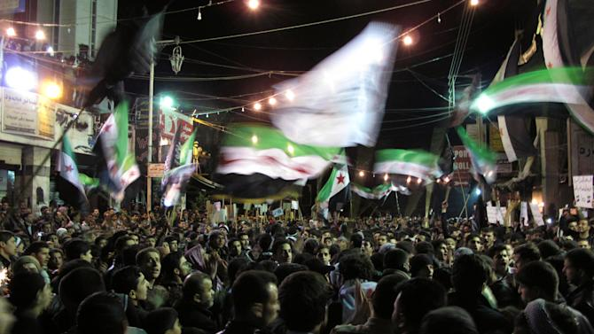 Syrians wave revolutionary flags and chant slogans at a night protest against President Bashar Assad in a neighborhood of Damascus, Syria, Monday, April 2, 2012. (AP Photo)