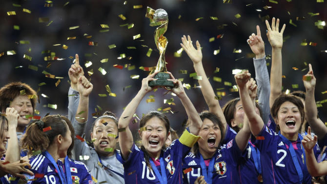 FILE - In this July 17, 2011, file photo, Japan players celebrate with the trophy after winning the final match between Japan and the United States at the Women's Soccer World Cup in Frankfurt, Germany. Leading up to the victory in Germany, Japan had been deeply scarred by the deadly earthquake and tsunami. The national team gave the country reason to cheer, and the players were welcomed home as heroes. (AP Photo/Michael Probst, File)