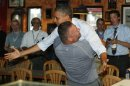 U.S. President Barack Obama is hugged by Scott Van Duzer at a pizza shop in Florida