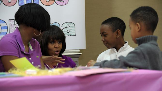 First lady Michelle Obama visits with, from left, Ashanti Ferguson and Samuel and Simeon Bright at the Fisher House, located at Walter Reed National Military Medical Center in Bethesda, Md., Wednesday, March 20, 2013, for a pre-Easter celebration with military families and children. (AP Photo/Susan Walsh)