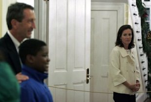 AP Photo/Brett Flashnick: South Carolina first lady Jenny Sanford, right, looks on as her husband Gov. Mark Sanford, takes a photo with guests at the Governor's Mansion in Columbia, S.C., during a Christmas Open House last week. Today, she filed for divorce.