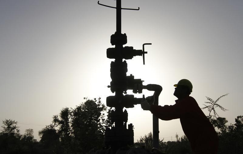 A technician opens a pressure gas valve inside ONGC group gathering station on the outskirts of Ahmedabad