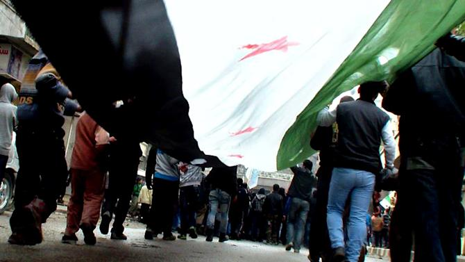 """This citizen journalism image provided by Aleppo Media Center AMC which has been authenticated based on its contents and other AP reporting, shows anti-Syrian regime protesters carrying a giant Syrian revolution flag, during a demonstration, in Aleppo, Syria, Friday, March 8, 2013. Syrian President Bashar Assad """"is not bluffing"""" about his determination to stay in power, Russia's foreign minister said in comments broadcast Friday, as negotiations to free 21 U.N. peacekeepers held by Syrian rebels dragged into a third day. (AP Photo/Aleppo Media Center AMC)"""